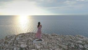 Вид с воздуха на женщине в длинном пинке, развевая платье стоит на крае скалы с взглядом сверху на море акции видеоматериалы
