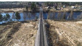 Вид с воздуха на мосте рельса через реку в населенном пункте сельского типа весной стоковая фотография