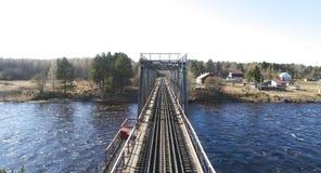 Вид с воздуха на мосте рельса через реку в населенном пункте сельского типа весной стоковое изображение rf