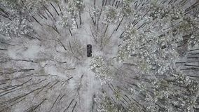 Вид с воздуха на SUV 6x6 которое едет дорогой зимы в покрытом снег лесе акции видеоматериалы