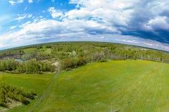 Вид с воздуха панорамы зеленых луга и поля около пути в форме небольшой планеты вокруг которой серые и белые облака стоковое изображение