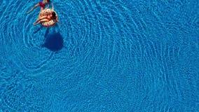 Вид с воздуха пар имея потеху в бассейне, человека плавает и женщина лежит на раздувном донуте видеоматериал