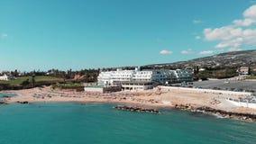 Вид с воздуха песчаного пляжа залива коралла в paphos Кипра с открытым морем и волнах на солнечный ветреный день Летание трутня н видеоматериал