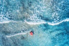 Вид с воздуха плавания молодой женщины с кольцом заплыва донута стоковые фотографии rf