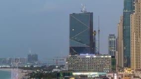 Вид с воздуха пляжа и туристов идя в JBR с днем небоскребов к timelapse ночи в Дубай, ОАЭ сток-видео