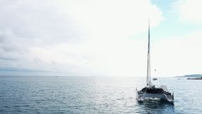 Вид с воздуха поставленной на якорь яхты катамарана стоящей и людей может загорающ на ем палуба сток-видео