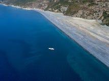 Вид с воздуха причаленной шлюпки плавая на прозрачное море Пляж черноты Nonza Корсика Франция Стоковые Изображения