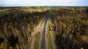 Вид с воздуха проселочной дороги через лес в осени фотография трутня стоковое фото rf
