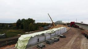 Вид с воздуха района строительства моста с 2 кранами близрасположенными проезжей частью и полем сток-видео