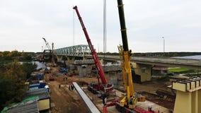 Вид с воздуха района строительства моста с 2 кранами близрасположенными проезжей частью и полем видеоматериал