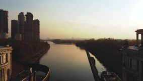 Вид с воздуха реки и большого города на заходе солнца Летание над небоскребами и рекой сток-видео
