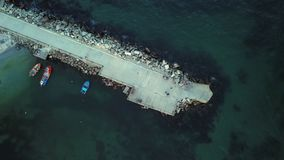 Вид с воздуха сигналит внутри небольшой пристани в море, небольшой причаленной шлюпке рыболовов акции видеоматериалы