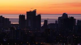 Вид с воздуха силуэтов небоскребов против захода солнца в большом городе акции видеоматериалы