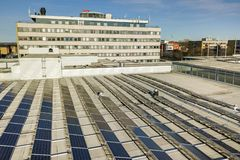 Вид с воздуха системы панелей голубого сияющего солнечного фото voltaic на коммерчески крыше производящ экологически чистую энерг стоковые изображения rf