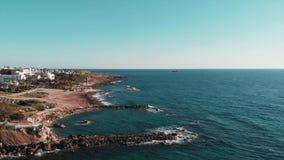 Вид с воздуха скалистого seashore в Кипре с гостиницами и полуостровом моря Трутень снятый пляжа острова скалистого и бурного col видеоматериал