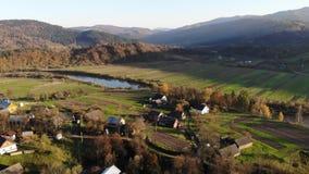 Вид с воздуха старой деревни Lastivka в Карпатах, Украине Время осени, заход солнца, и красивый ландшафт Ровный полет сток-видео