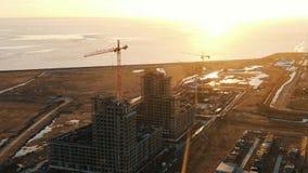 Вид с воздуха строительной площадки с кранами конструкции на заходе солнца сток-видео