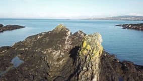 Вид с воздуха тени трутня летая над утесами на заливе быков на Anglesey - Уэльсе - Великобритания сток-видео