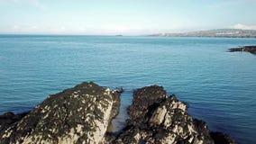 Вид с воздуха тени трутня летая над утесами на заливе быков на Anglesey - Уэльсе - Великобритания видеоматериал