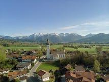 Вид с воздуха традиционной деревни в Баварии с горными вершинами на заднем плане стоковое фото
