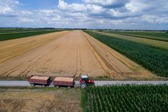 Вид с воздуха трактора с трейлерами на сельской дороге Стоковая Фотография