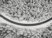 Вид с воздуха трутня дороги в снежном лесе стоковые фотографии rf