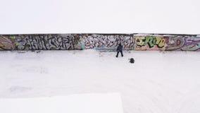Вид с воздуха художника улицы в темных одеждах распыляя граффити на стене в зиме E Искусство улицы стоковое фото