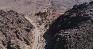 Вид с воздуха черного вождения автомобиля на проселочной дороге в горе Кинематографическое летание съемки трутня над дорогой грав акции видеоматериалы