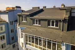 Вид с воздуха экстерьера комнаты дополнения чердака с пластиковыми окнами, крышей и стенами покрытыми с планками коричневого мета стоковая фотография