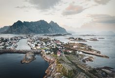 Вид с воздуха Henningsvaer, своего сценарного футбольного поля и гор на заднем плане Henningsvaer рыбная ловля стоковое фото