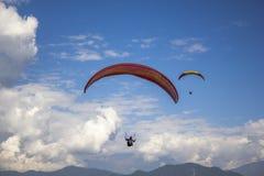 Вид с воздуха 2 pargliders на красных желтых парашютах летая в голубое небо с белыми облаками над горами стоковое фото