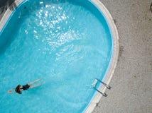Вид с птичьего полета открытого бассейна и длинные волосы чернят заплывы девушки купальника в воде стоковая фотография