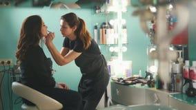 Визажист в салоне красоты делает для состава привлекательной девушки красивого, парикмахера делает стиль причёсок, конец вверх акции видеоматериалы