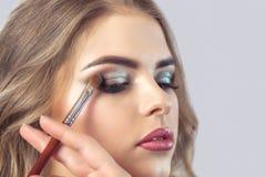 Визажист делает закоптелый макияж глаз стоковое изображение
