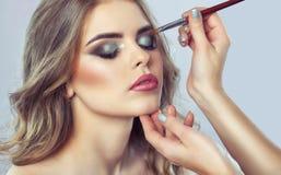 Визажист делает закоптелый макияж глаз применяться составляет стоковые фотографии rf