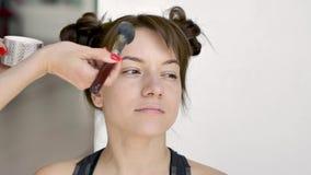 Визажист делает макияж красивого молодого кавказского брюнета видеоматериал