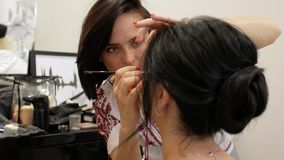 Визажист делает макияж красивой девушки брюнета стилизатор работая на изображении модели визажист рисует глаза с сток-видео