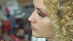 Визажист делает для того чтобы компенсировать красивую женщину Smokey наблюдает для фотомодели сток-видео