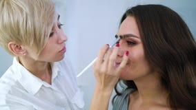 Визажист крупного плана женский прикладывая косметики на красивой стороне женщины с щеткой на салоне красоты сток-видео