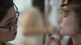 Визажист прикладывает губную помаду к губам усаженной женщины внутри помещения сток-видео