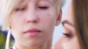 Визажист прикладывая косметики на крупном плане стороны молодой женщины видеоматериал
