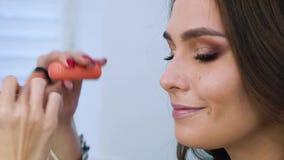 Визажист прикладывая косметики на крупном плане стороны молодой женщины акции видеоматериалы
