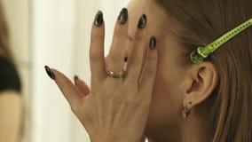 Визажист прикладывая сливк косметик на фотомодели стороны кожи перед выражением лица Закройте вверх по стороне женщины пока соста видеоматериал