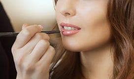 Визажист прикладывает маленькую девочку состава красивую, губную помаду с профессиональной щеткой стоковое изображение rf