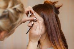 Визажист прикладывает состав и делает вкладыш глаза с профессиональной щеткой в салоне красоты стоковая фотография rf