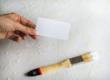Визитная карточка на предпосылке щетки картины и белизны заштукатурила стена стоковое фото