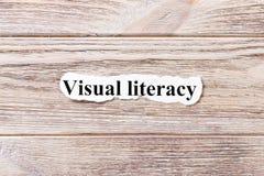 Визуальная грамотность слова на бумаге Концепция Слова грамотности Avisual на деревянной предпосылке стоковые фото