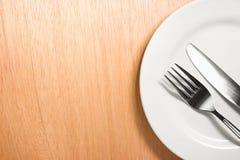 Вилка и нож с белой плитой на деревянной предпосылке Стоковое Изображение