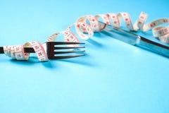 Вилка и нож с сантиметром на голубой предпосылке, диета, здоровый образ жизни стоковые фото