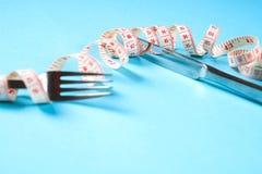Вилка и нож с сантиметром на голубой предпосылке, диета, здоровый образ жизни стоковые изображения
